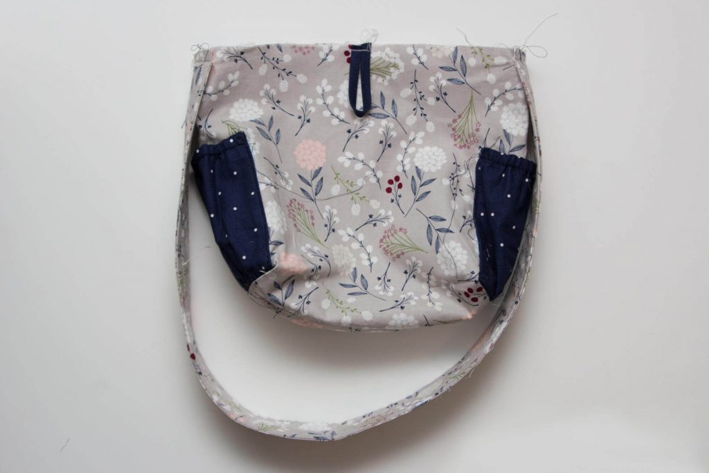 c77d732914b2 По бокам сумочки примётываем вручную ручки и петлю для пуговицы. Снова  выворачиваем сумку наизнанку.